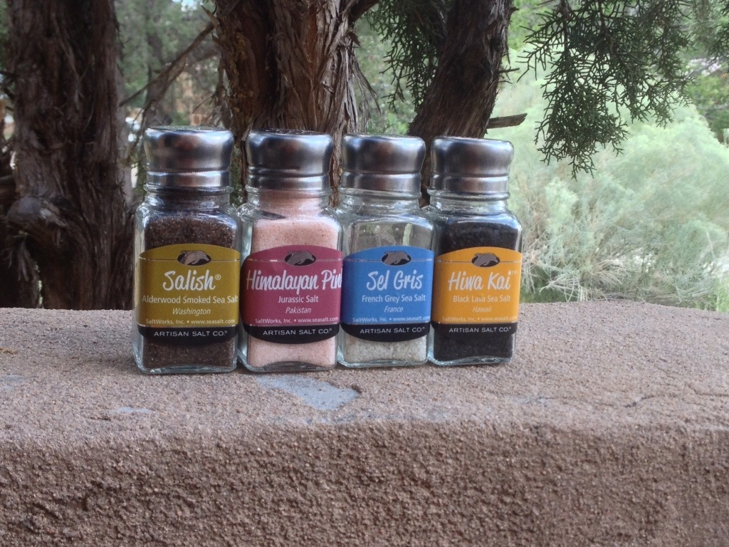 Picture of a series of salt shakers with different types of salts and their labels.
